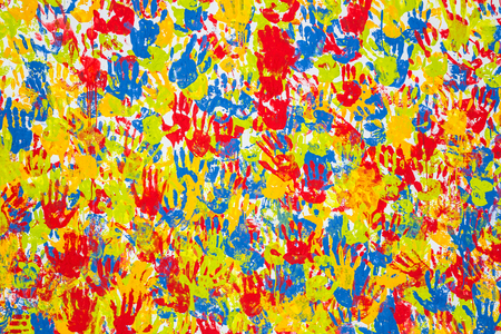 Seamless hands background isolated on white - teamwork concept. Imprint of the childrens palm on the canvas. Prints of colored hands. Many childrens colorful hands. Stock fotó