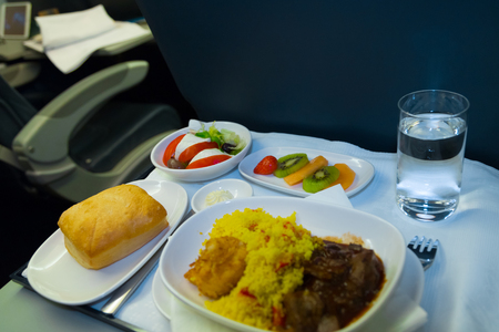 Food served on board of business class airplane on the table. Tray of food in the airplane. Tray of food on the plane, business class travel. Prepared food on the plane