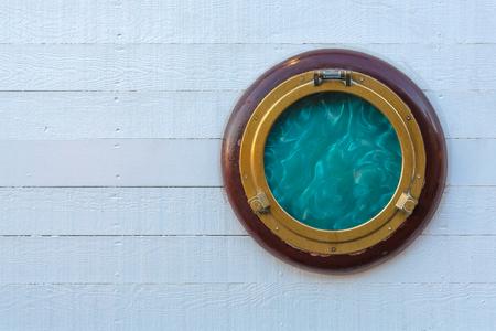 Ship golden portholes on white wooden background. Ship window or porthole on white wooden wall.