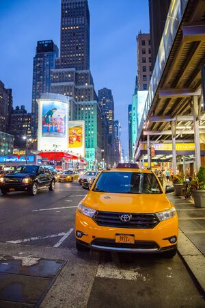 New York, United States - jun 21, 2016: Yellow taxi on the street in New York. Yellow cab is parked near a large hotel in New York.