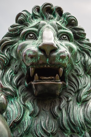 Lion statue aged. Close up of the head of a bronze sculpture of a lion. Large bronze lion statue sculpture in outdoor setting. Banco de Imagens