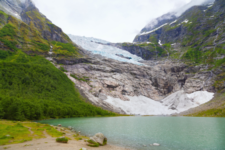 Landscape with river near Briksdal or Briksdalsbreen glacier in Olden, Norway with green mountain. Norway nature and travel background. Summer in Norway, glacier Briksdalsbreen Banco de Imagens
