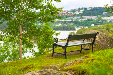 Bench without people in a picturesque place in nature. Bench overlooking the pond near the house of Edvard Grieg.
