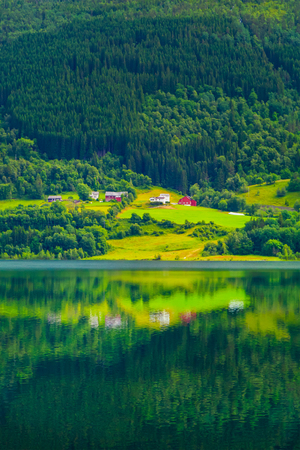 Colorful village on the shore of alpine lake, at the foot of wooded mountain slope. A small village with modern houses by the lake, Norway. Environmentally friendly living environment. Banco de Imagens