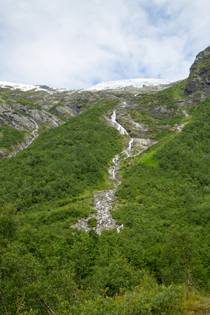 Melting Briksdal glacier in Norway. Scenery Waterfall In Briksdal Glacier In Norway. Beautiful waterfall from the meltwater of the Brixdal Glacier in Norway, bottom view. Stock Photo