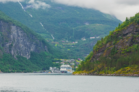 Ferry ship with cars and passengers on Norwegian fjord. Norway nature and travel background. Cruise ship sailing along the fiord. Ferry to Scandinavia. Cruise ship. Tourism holidays and travel.