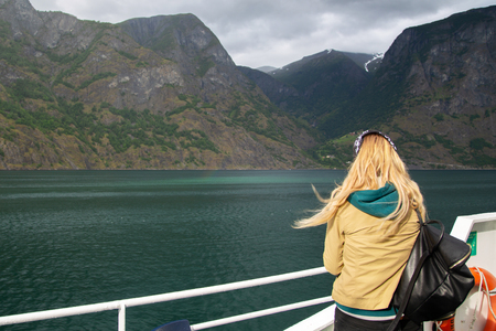 Young woman with a backpack on the deck of the ferry looks at the Norwegian fjords. Woman blonde tourist on a ship admires the nature of Norway. A young woman travels alone. Tourist concept.