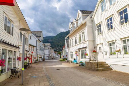Nordfjordeid, Norway - July 2016: Main street of the Nordfjordeid town with a retro white buildings. Curvy street with old nice white houses in historical center of Nordfjordeid town, Norway