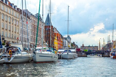 Copenhagen, Denmark - June 2016: Scenic summer sunset view of Nyhavn pier with color buildings, ships, yachts and other boats in the Old Town of Copenhagen, Denmark