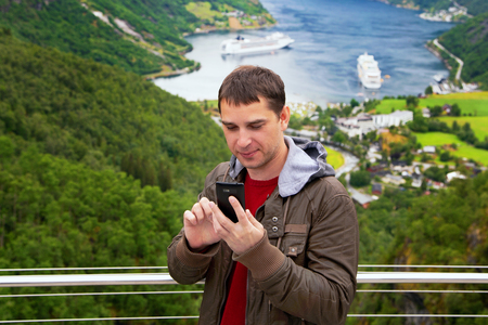 Men poses on camera and does selfi near Geiranger, Norway. End of the famous Geiranger fjord, Norway with cruise ship, top view. Geiranger View Point. Tourism holidays and travel.