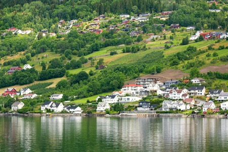 Village is located on the green slopes near lake. Scenic summer view of cottage houses in mountain village near lake, Norway. Tourism holidays and travel.