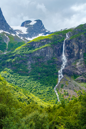Norway landscape with big waterfall. Waterfall in mountains of Norway. Tourism holidays and travel.