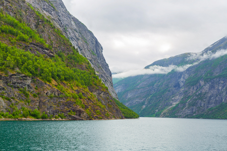 Fjord in Norway - nature and travel background. Beautiful Nature Norway natural landscape. Trip by ship through the fjord. Fjord And Mountain With Snow on the Norway.