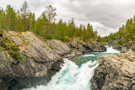 Mountain wild river valley landscape. landscape along river Finna in province of Oppland, and Polfossen waterfall, Norway. Raging mountain river in green valley. Norway nature and travel background.