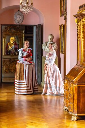 Hillerod, Denmark - June, 2016: Renaissance Style - beautiful young women in magnificent dresses in an old palace interior. Two young women in baroque dresses in the interior of an old baroque castle.