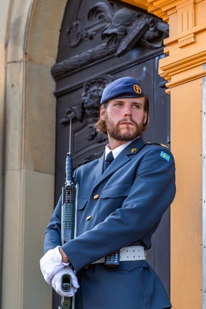 Stockholm, Sweden - June 2016: Royal Swedish guardsman with beard in a modern uniform with a gun on the guard of the Royal Palace in the capital of the country.