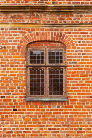 Brick wall of old castle with window. Glass panel window in a brick wall. A window in an old brick building. Background of old vintage brick wall and an old wooden window. Banco de Imagens