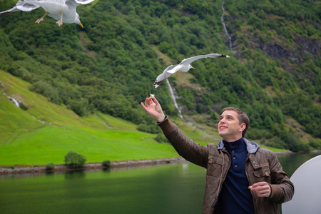 Tourist feeding bread to seagulls. Young man feeding seagulls flying over the ferry boat. Man traveling on ferry boat and feeding seagull. Tour of Norway. Tourist feeds seagulls from deck of the ship. Banco de Imagens