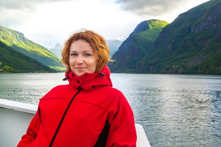 Young beautiful woman in smiling against the background of a Norwegian fjord. Journey through Norwegian fjords. Woman on the deck of a ship in Norway looking at the camera, close up. Tourist concept. Banco de Imagens