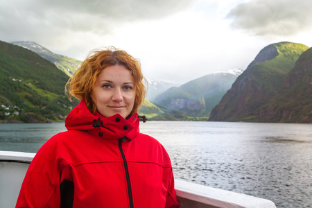 Young beautiful woman in a red jacket on the background of Norwegian fjord. Journey through the Norwegian fjords. Woman on the deck of a ship in Norway. Red-haired freckled young woman in red jacket.