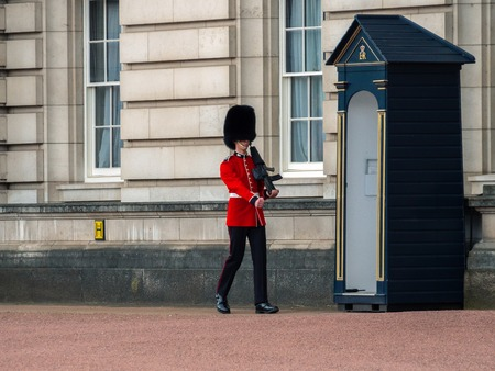 London, UK - April, 2019: English guard patrolling in London. Solider of Buckingham palace, London England. Sentry on duty at Buckingham Palace.