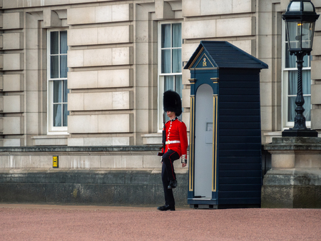 London, UK - April, 2019: A soldier of the English Guard patrols near Buckingham Palace in the service of the Queen of England. The soldier is dressed in the form of a royal guard.