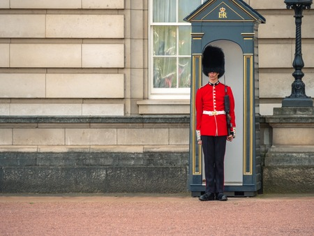 London, UK - April, 2019: A Guard standing outside Buckingham Palace. English guard patrolling in London. Solider of Buckingham palace, London England.