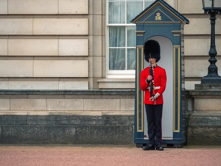 London, UK - April, 2019: The Queens Guard on duty at Buckingham Palace, the official residence of the Queen of England. Solider of Buckingham palace, London England.