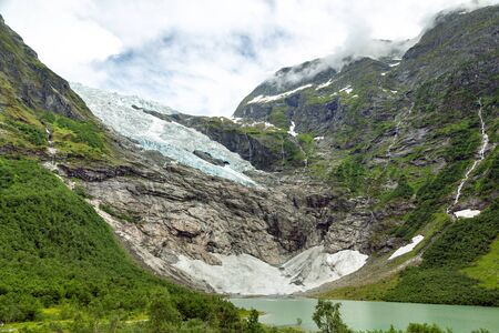 Landscape with river near Briksdal or Briksdalsbreen glacier in Olden, Norway with green mountain. Norway nature and travel background. Summer in Norway, glacier Briksdalsbreen 写真素材