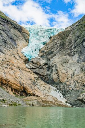 Melting Briksdal glacier in Norway, close up. Panorama from bottom to top. Norway nature and travel background.