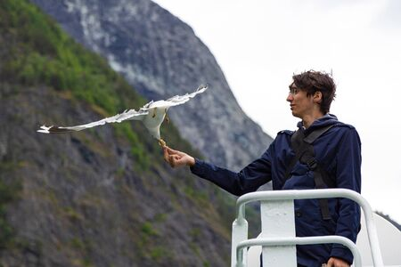 Young man feeding seagulls flying over the ferry boat. Journey through the Norwegian fjords. Tour of Norway. Tourist feeds seagulls from the deck of the ship. Tourist route in Norway. Sea gull is flyi