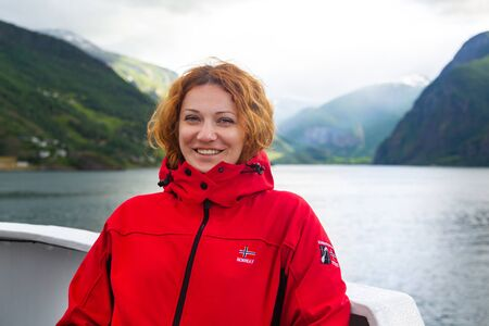 Young beautiful woman in smiling against the background of a Norwegian fjord. Woman on the deck of a ship in Norway. Journey through the Norwegian fjords. Tourist concept. Journey on the ferry boat.