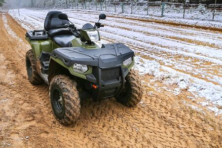 ATV stands on winter background on the state border. Quad bike in the sand. Quad bike in service at the border.