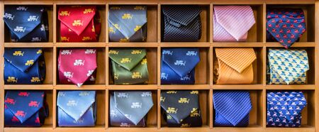 Showcase with multicolored ties. View of different colors ties in showcase. Multicolored man. Showcase of rolled neckties at store. Coiled ties on shelf at shop. Twisted neckties beautifully stacked. 写真素材