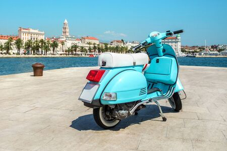 Blue retro scooter is parked in a city near the sea with a helmet. Blue vintage scooter stands on the waterfront on the background the old city in sunny weather. Split, Croatia. Travel concept. 写真素材