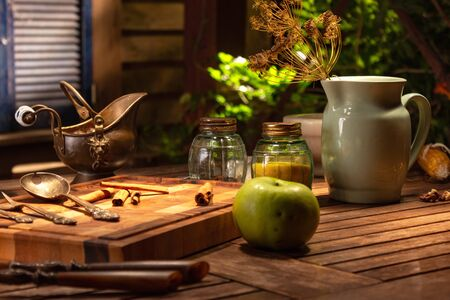 Still life with a porcelain vintage jug and antique spice jars and green apple. Still life in vintage rural style with dry spices. Copper vintage jug on a wooden table. Cinematic lighting still life.