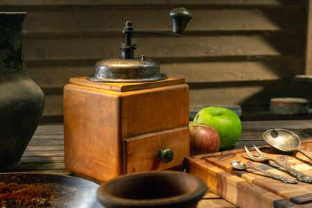 Rustic wooden vintage coffee grinder, closeup. Still life with old coffee mill and antique dishes on the wooden background. Nostalgic coffee grinder on old table and textured wood background.