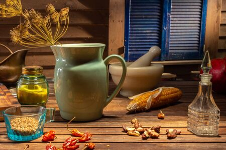 Still life with a porcelain vintage jug and antique spice jars. Still life in vintage rural style with dry spices. Vintage still life with utensils on a wooden table with cinematic lighting. Stock fotó