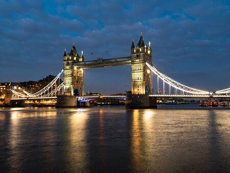 Tower Bridge nocą oświetlony przez reflektory. Słynny Tower Bridge wieczorem z błękitnym niebem i refleksem na wodzie, Londyn, Anglia. Nocny pejzaż z Tower Bridge, Londyn, Wielka Brytania.
