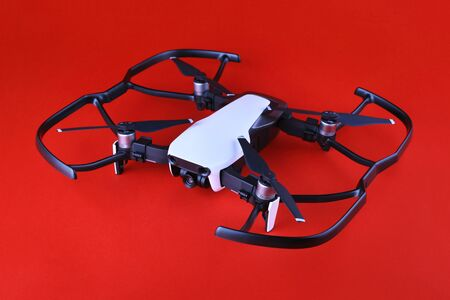 Uav drone copter isolated on white background, close-up. Small drone quadrocopter with propeller protection on a red background. Safe drone flight. Unmanned aerial vehicle on a red background.