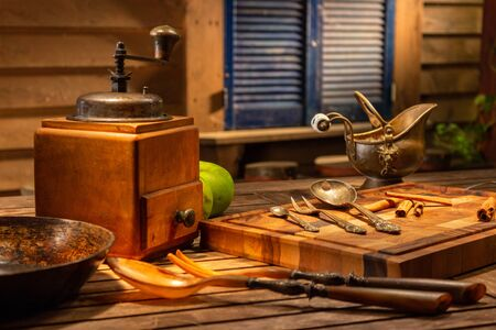 Vintage still life with old copper vintage jug on a wooden brown table. Still life with old coffee mill and antique dishes on the wooden background. Vintage tablespoons and forks. Archivio Fotografico