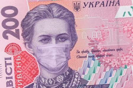 200 hryvnia banknote with Lesya Ukrainka in a medical mask, horizontal. Economic crisis has affected Ukraine. Ukrainian money, coronavirus concept, montage, close up. COVID-19 coronavirus in Ukraine. 免版税图像