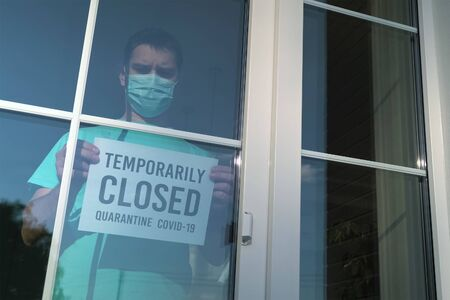 Man with Temporarily Closed sign during quarantine 스톡 콘텐츠