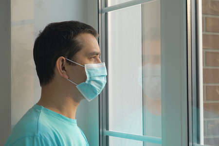 Quarantine self-isolation. Sad young man in a medical mask who looks out the window through the window. Infected man in medical mask on self-isolation looks at the street through the window of a house Zdjęcie Seryjne