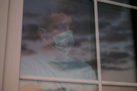 Self isolation for distancing. Waiting for quarantine to be canceled. Portrait of a sad young man in a medical mask who looks out window. Sadness and longing during quarantine of Coronavirus COVID-19. 스톡 콘텐츠