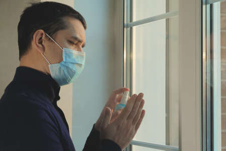 Quarantine self-isolation. Sad young man in a medical mask who looks out the window through the window. Infected man in medical mask on self-isolation looks at the street through the window of a house 스톡 콘텐츠
