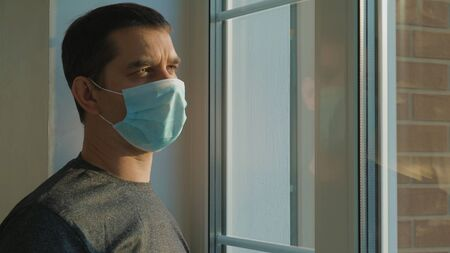 Man in surgical mask looking out his home window.