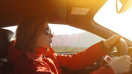 Young woman is driving a car on a sunny day.