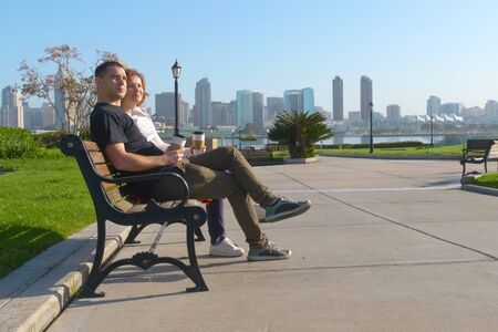 Couple relaxing on San Diego City bench. In the background is the downtown San Diego with skyscrapers. Concept about love, relationship, and travel. Young couple resting on the promenade in the city. 스톡 콘텐츠