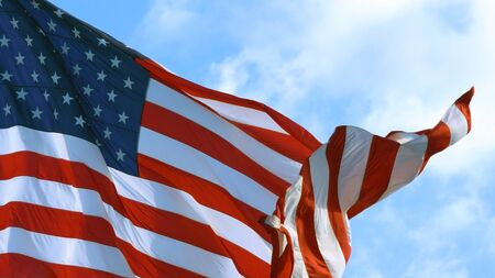 Close up of USA flag waving in the wind on a bright sunny day. Coseup of American Flag gracefully waving in wind.